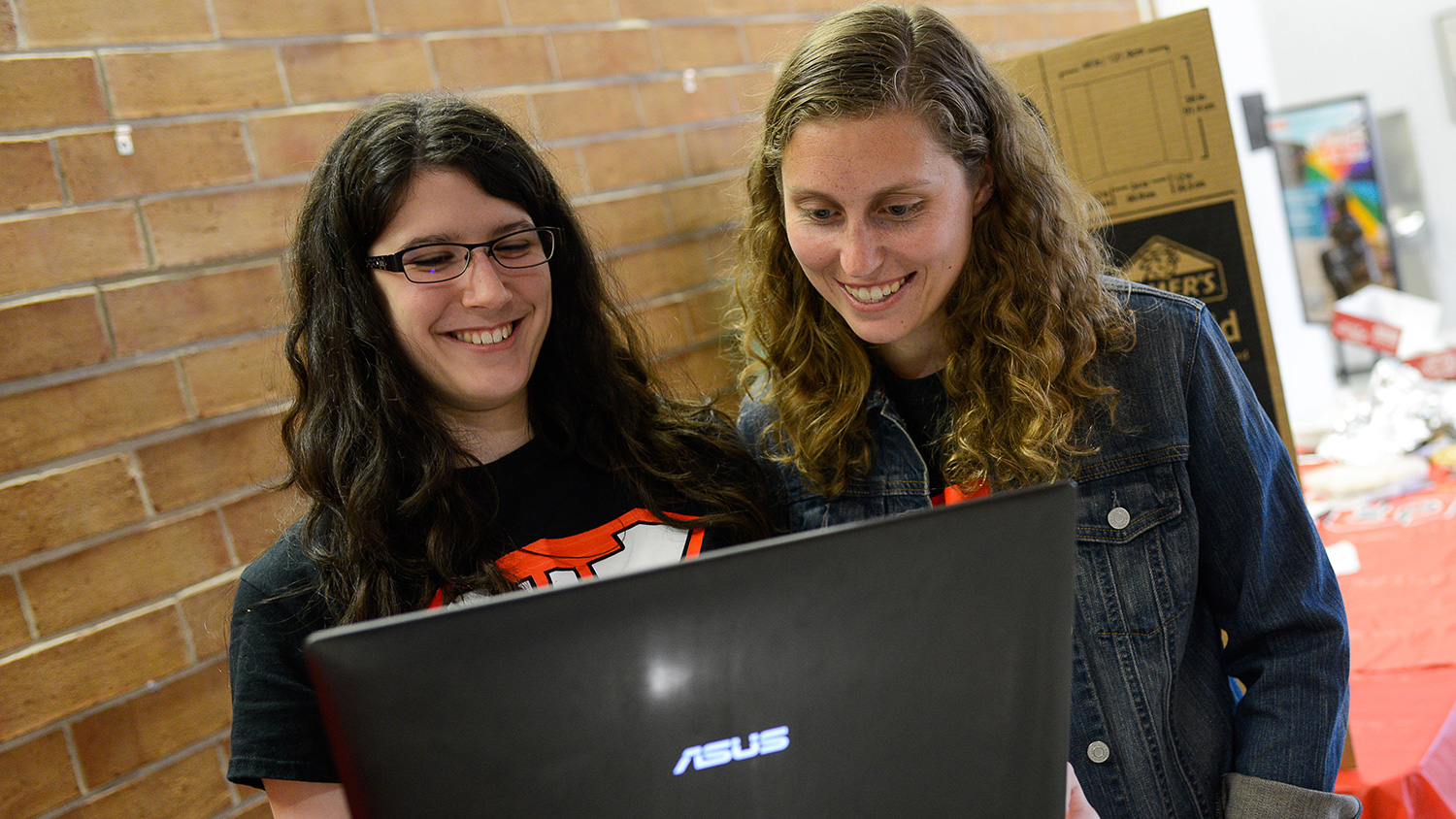 Two female math students look at a laptop